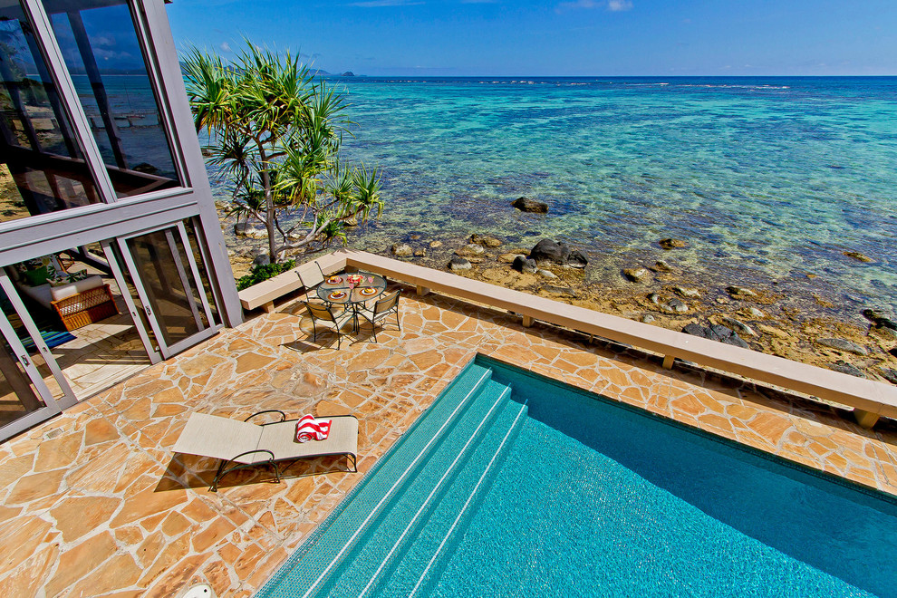 Patio - large tropical backyard stone patio idea in Hawaii with no cover