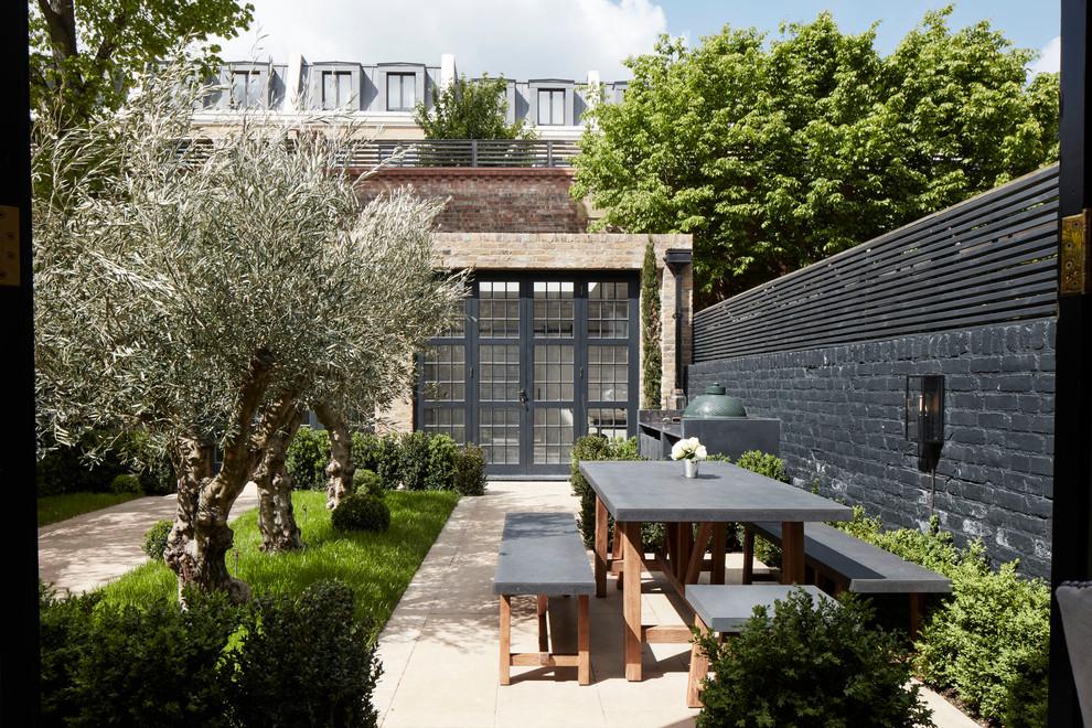 Mid-sized elegant backyard stone patio photo in London