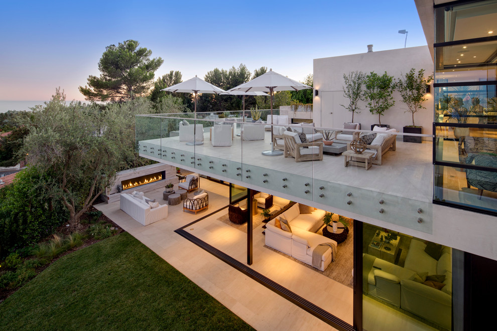 Huge trendy backyard tile patio photo in Los Angeles with a fire pit and a roof extension
