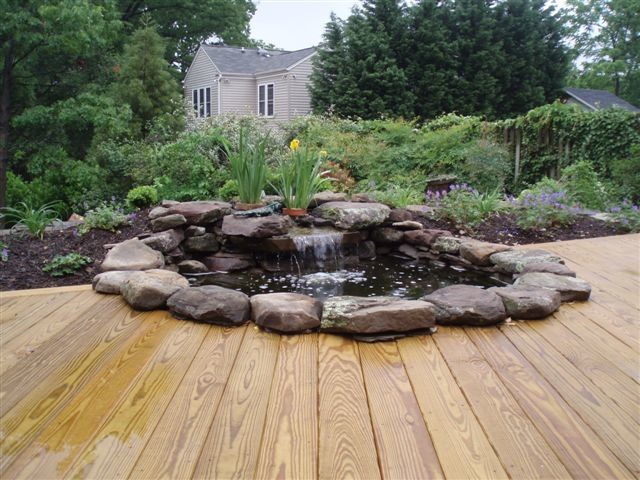Waterfall pond with wood stained deck contemporary for Deck pond ideas