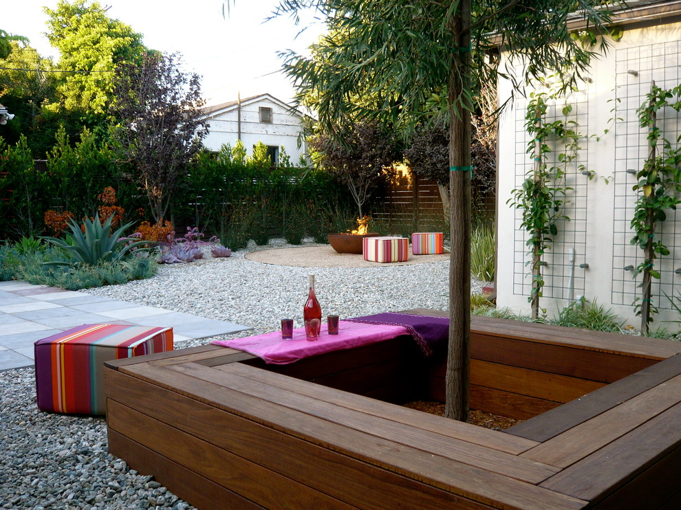 Example of a trendy backyard concrete paver patio design in Los Angeles with a fire pit