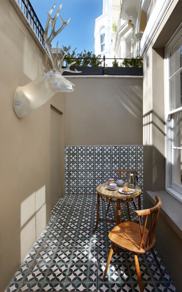 Inspiration for a small eclectic tile patio remodel in London with no cover