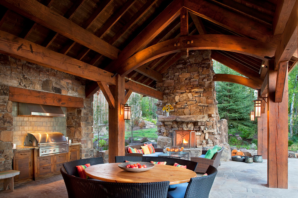 Inspiration for a rustic patio remodel in Other with a fire pit and a roof extension