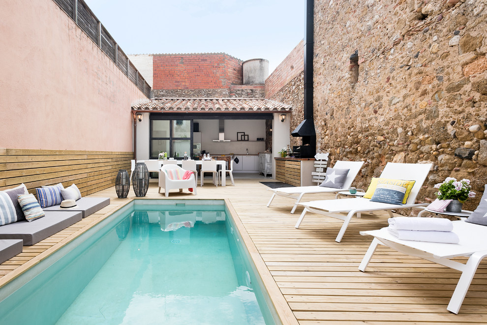 Mid-sized tuscan backyard rectangular lap pool house photo in Barcelona with decking