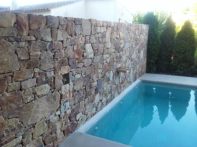 Detalle de muro de piedra natural frente a piscina con - Muro de piedra natural ...