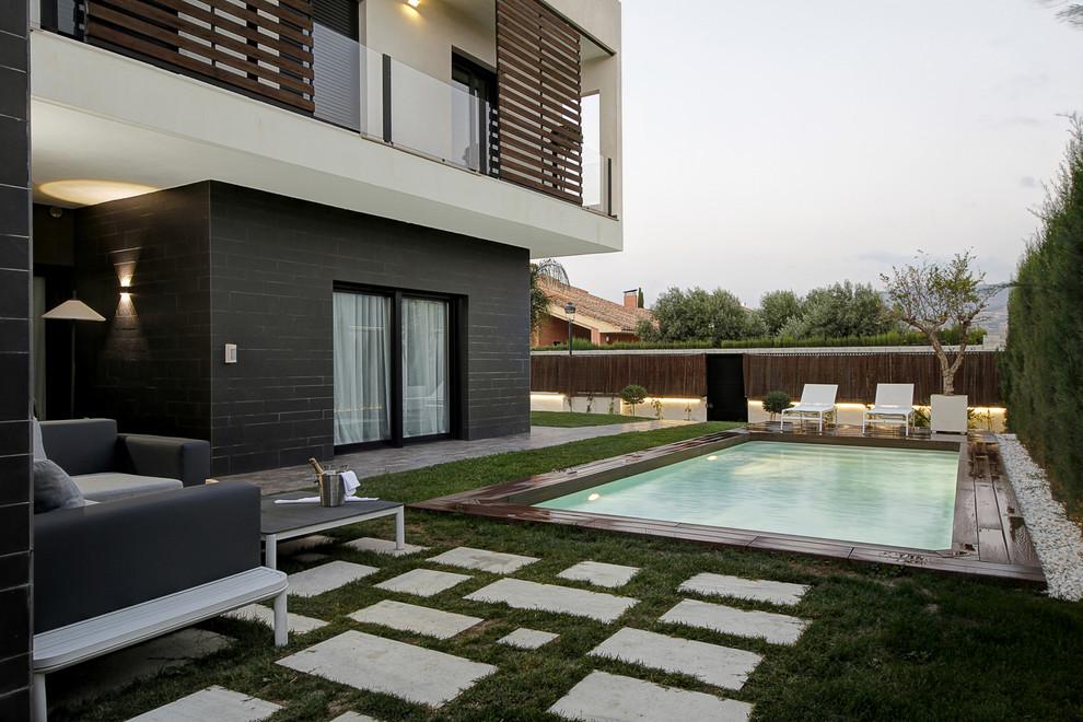 Diseño de piscina alargada, moderna, rectangular, en patio trasero, con adoquines de hormigón