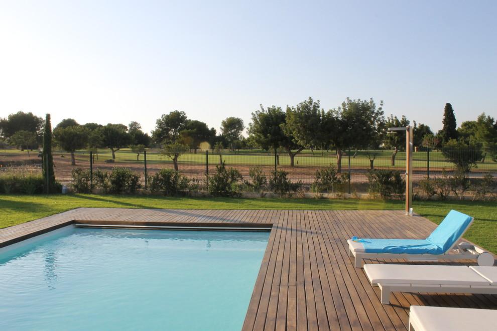 Ejemplo de piscina alargada, rural, grande, rectangular, en patio trasero, con entablado