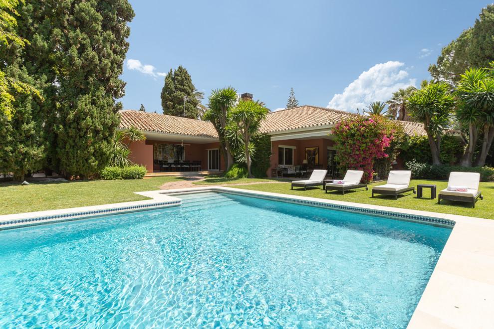 Ejemplo de piscina tropical, grande, rectangular, en patio delantero