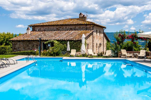 Esempio di una piscina country personalizzata dietro casa con piastrelle
