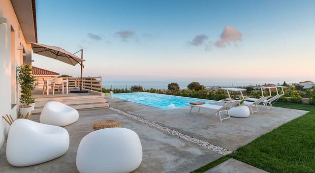 Ispirazione per una piscina a sfioro infinito design rettangolare con lastre di cemento