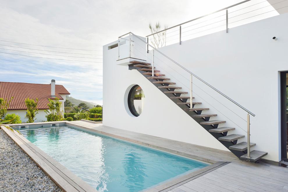 Diseño de piscina alargada, minimalista, grande, rectangular, en patio lateral, con entablado