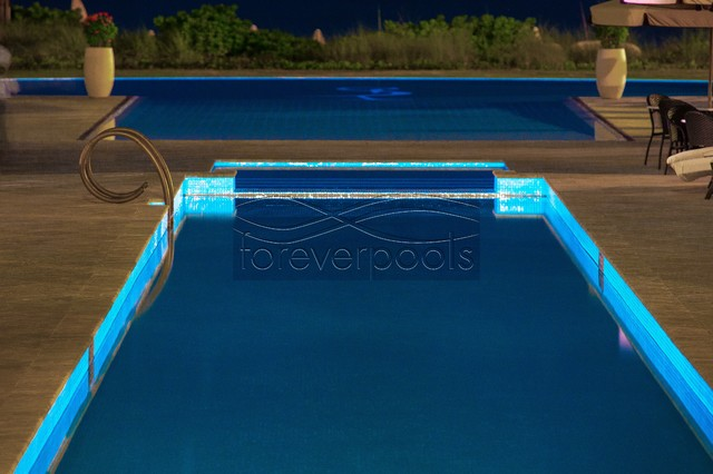 1 Resurface of a hotel pool w/glass tile (night time) modern-pool