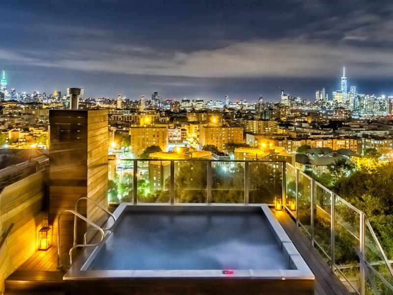Minimalist rooftop rectangular aboveground hot tub photo in New York with decking