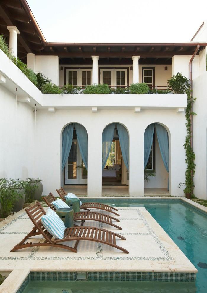 Tuscan courtyard custom-shaped pool photo in Miami