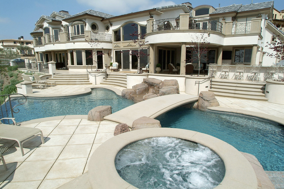 Example of a huge tuscan backyard concrete paver and custom-shaped natural hot tub design in Los Angeles