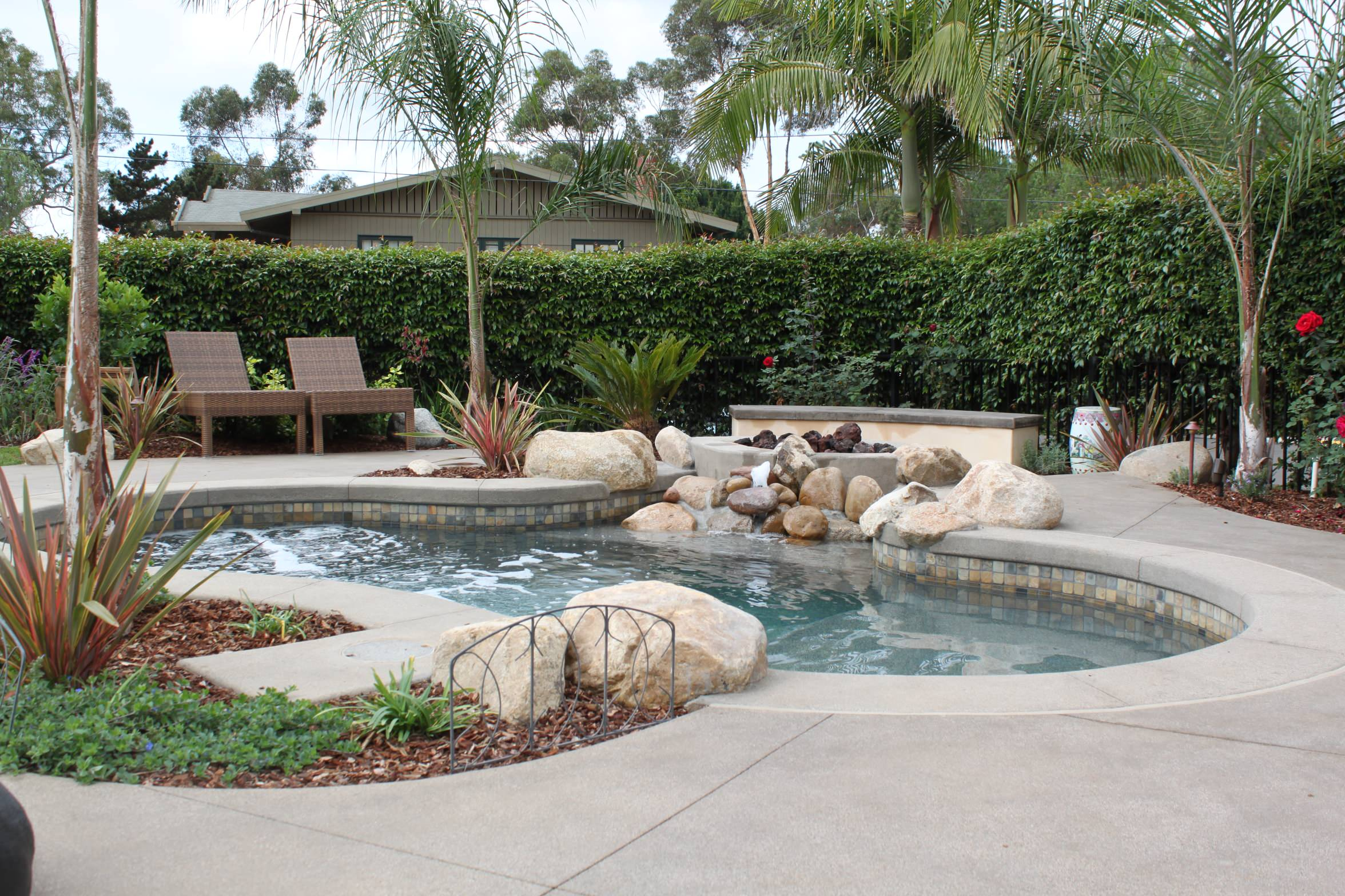 A Spool, Spa and Pool Combination with Fire Pit Above