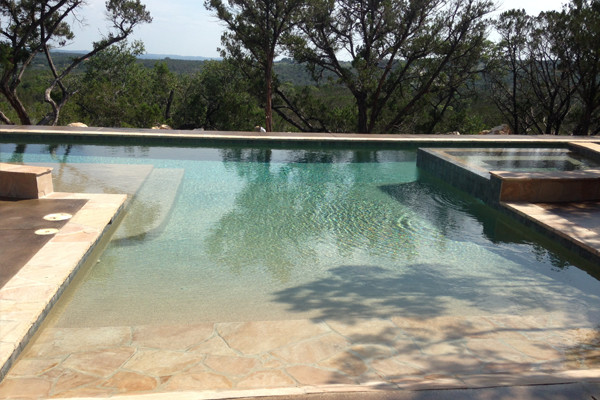 Inspiration for a large modern backyard custom-shaped lap hot tub remodel in Austin with decking