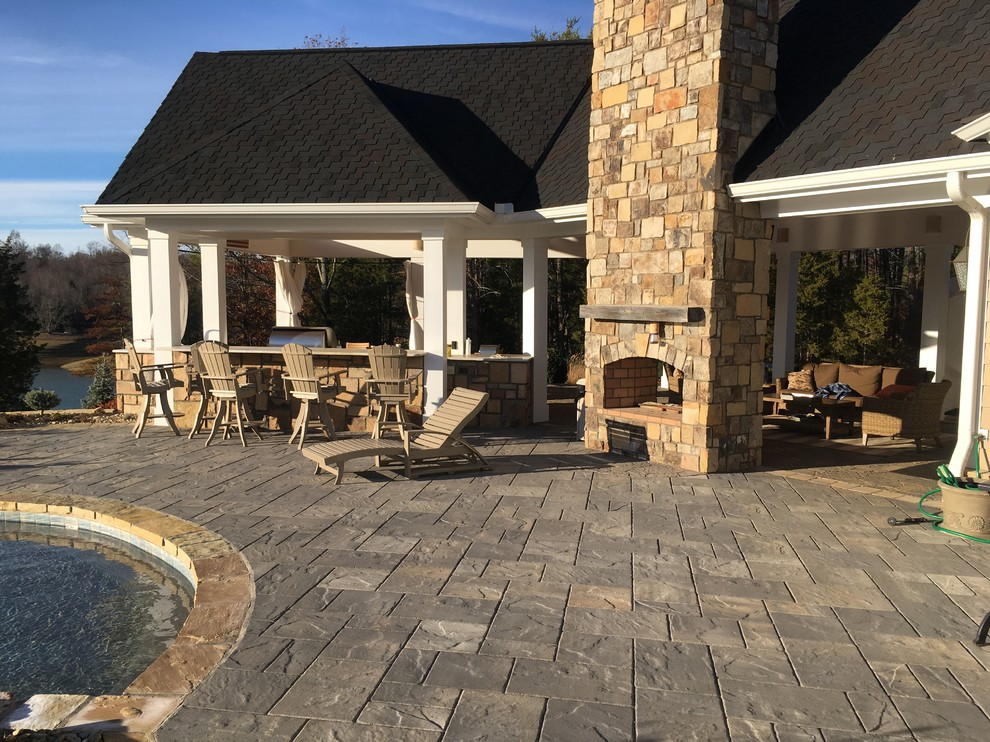 Large farmhouse backyard concrete paver and custom-shaped infinity hot tub photo in Other