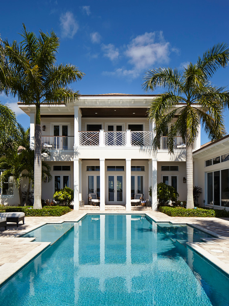 Inspiration for a large coastal backyard custom-shaped lap pool remodel in Miami
