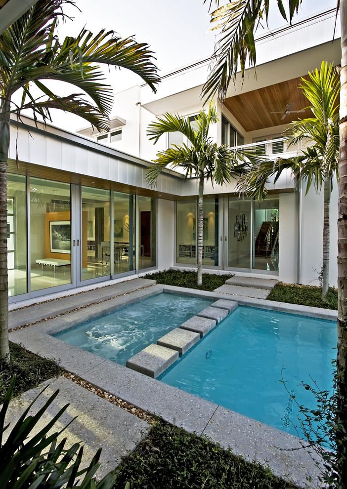 Pool - small modern courtyard rectangular pool idea in Miami