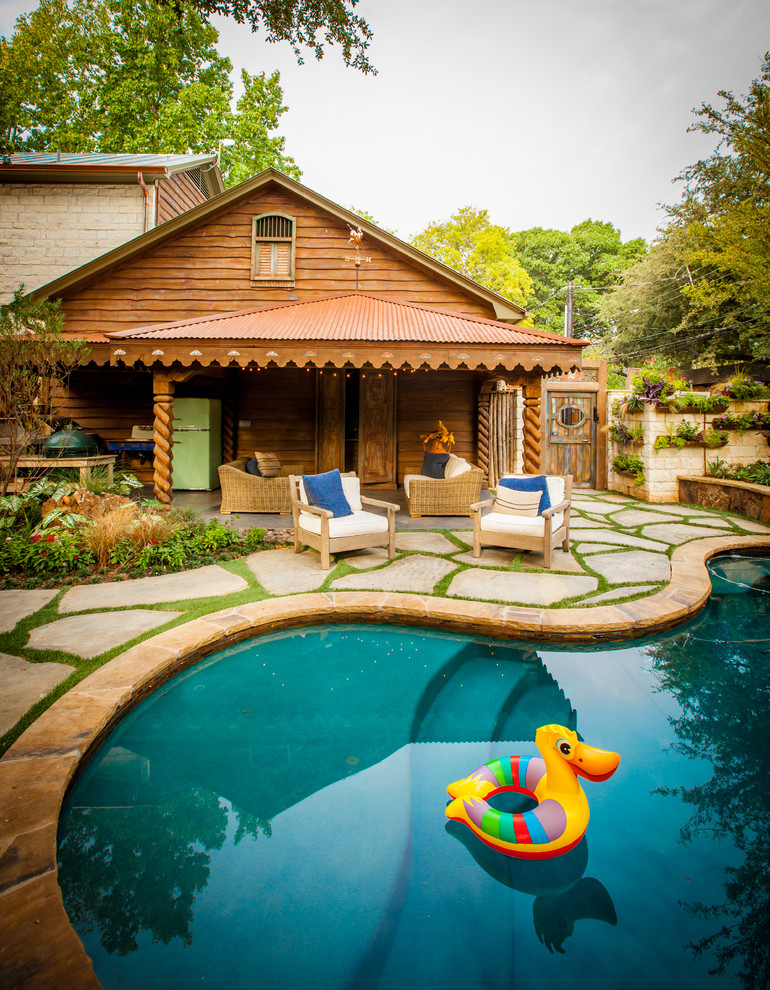 Mountain style kidney-shaped pool photo in Dallas