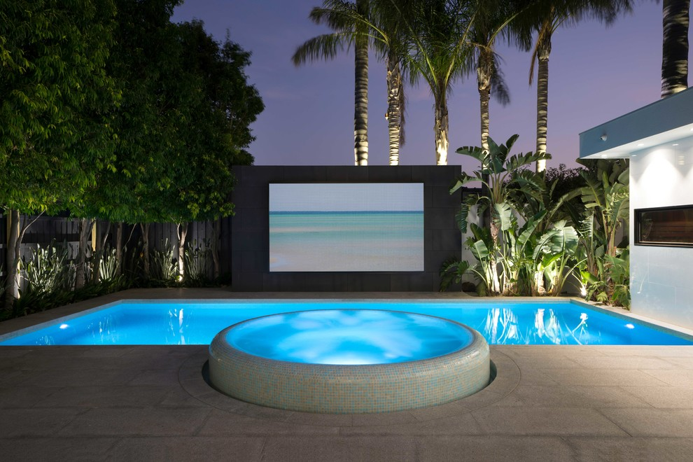 Example of a large minimalist backyard stone and rectangular lap hot tub design in Melbourne