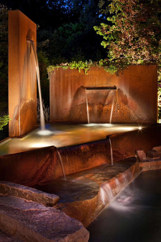 Example of a mid-sized minimalist backyard stone and custom-shaped aboveground pool fountain design in Detroit