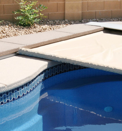 This close up of an automatic pool cover track gives you an idea on how an automatic pool cover works, sliding the rolled cover along the track, unrolling it as it crosses the distance.