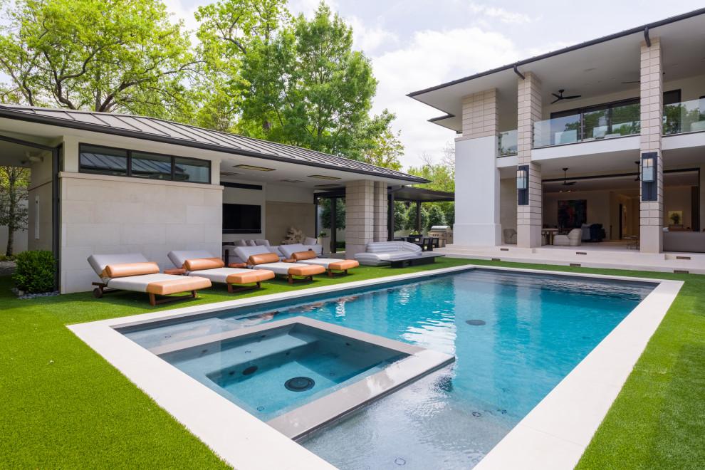 Pool house - huge 1960s backyard stone and rectangular pool house idea in Dallas