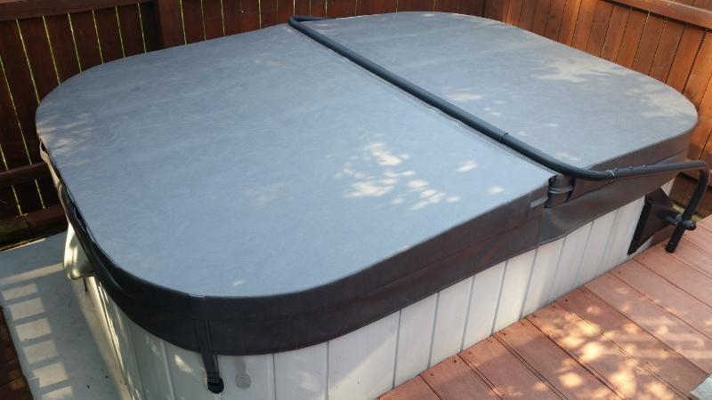 Mid-sized elegant backyard custom-shaped hot tub photo in Wilmington with decking