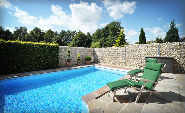 Foto de piscina actual, de tamaño medio, rectangular, en patio trasero, con adoquines de piedra natural