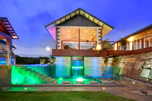 With a clear glass pool fence, you can play with pool lights to make an interesting visual element to your pool at night.
