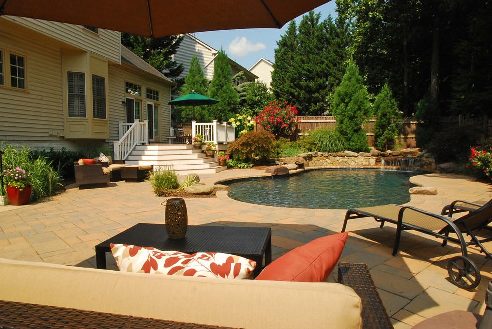 Foto de piscina con fuente natural, ecléctica, de tamaño medio, a medida, en patio trasero, con adoquines de hormigón