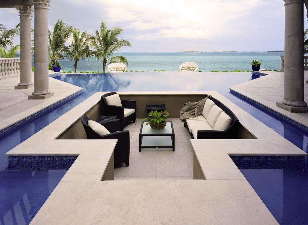 Huge elegant backyard tile and custom-shaped infinity pool photo in Other