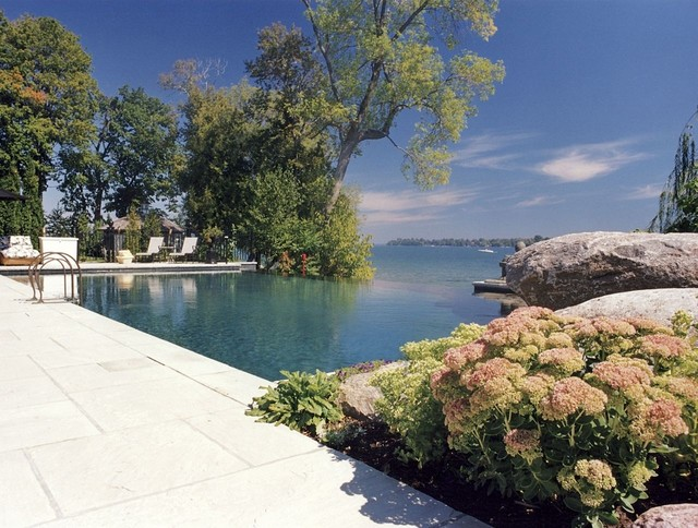 Example of a large trendy backyard stone and rectangular infinity pool design in Toronto