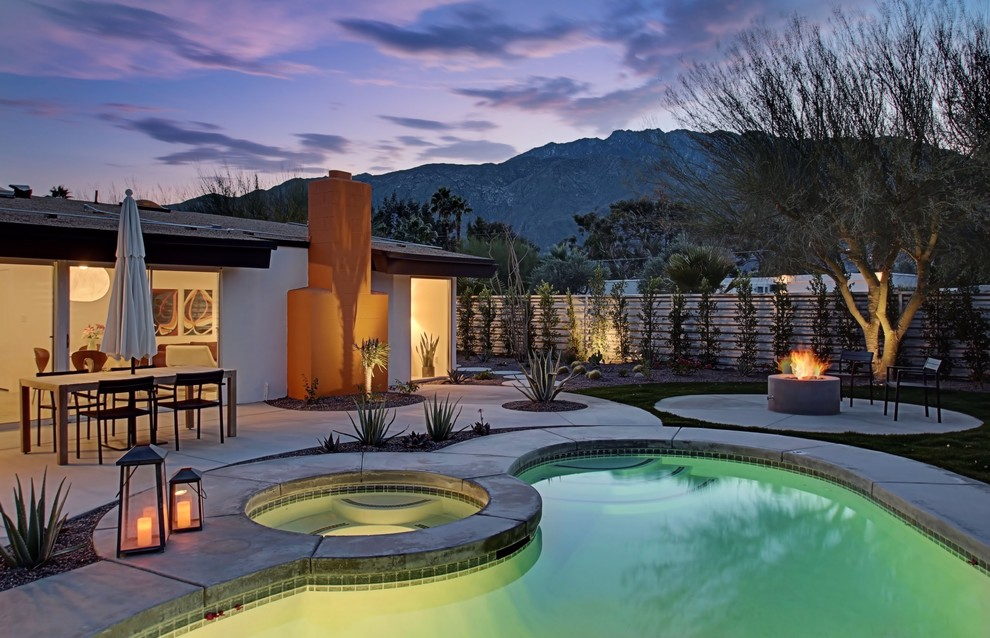 Inspiration for a mid-sized 1950s backyard concrete paver and kidney-shaped hot tub remodel in Los Angeles
