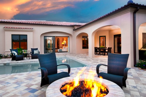 Mediterranean style swimming pool with firepit