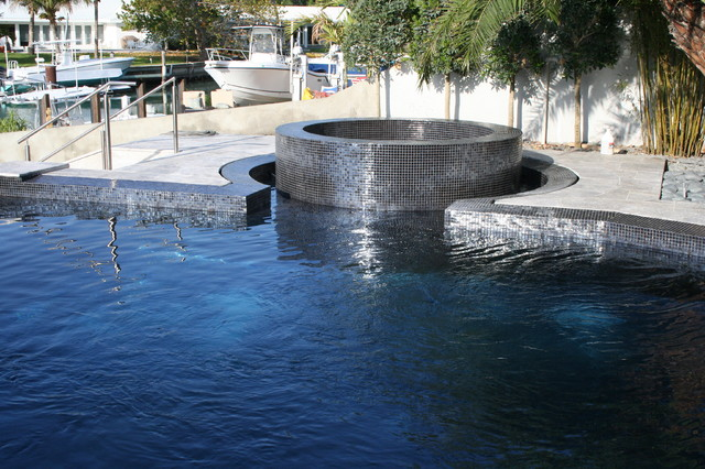 Iridescent black glass tile pool with perimeter overflow at both pool ...
