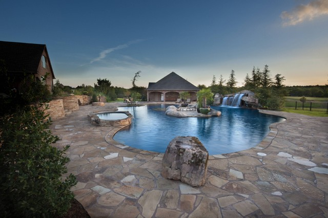 Glass Tiled Pool With A Rustic Island Oasis in Oklahoma tropical-pool