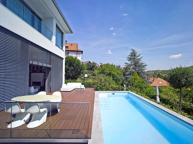 Diseño de piscina alargada, actual, grande, rectangular, en patio lateral, con entablado
