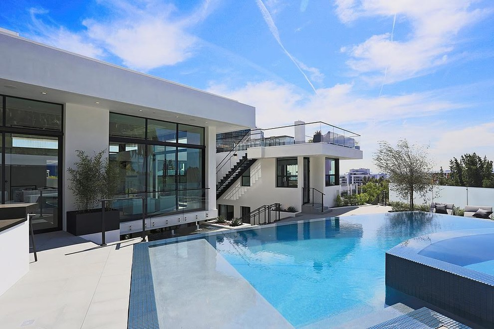 Huge trendy backyard concrete and rectangular infinity hot tub photo in Los Angeles