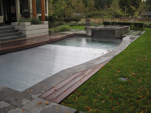 A Ridged automatic cover on this pool. The automatic cover here lays under the lip of the pool, and is made from a ridged material. The harder material adds to the durability of the cover.