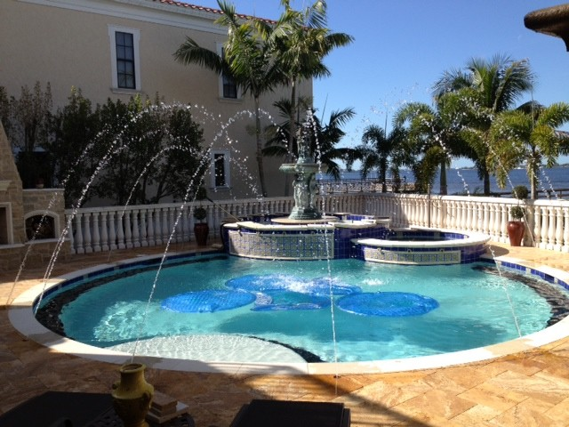 Mid-sized island style backyard tile and round hot tub photo in Miami