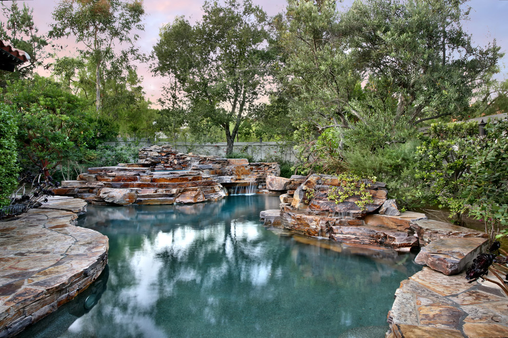 Example of a large mountain style backyard custom-shaped and stone natural pool design in Orange County