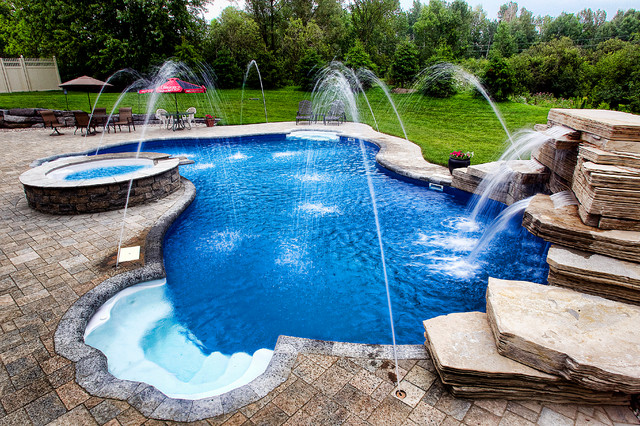 Inground pool with fountains, waterfall, and built in spa