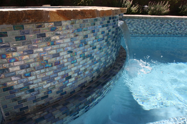 "Iridescent blue 1"" X 2"" glass tile surrounds the pool and ..."