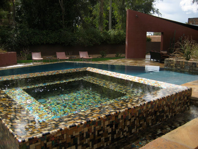 Iridescent mosaics shimmer under water in this beautiful infinity edge spa. modern-pool