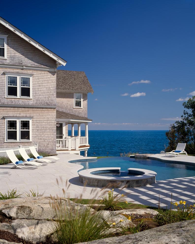 Large ornate side yard stone and custom-shaped infinity hot tub photo in Boston