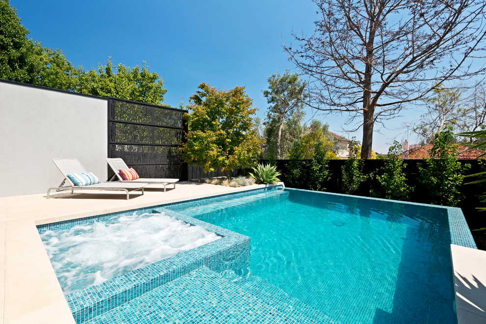 Pool - large contemporary backyard concrete paver and rectangular infinity pool idea in Melbourne