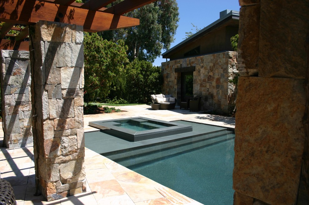 Hot tub - large contemporary backyard stone and rectangular infinity hot tub idea in Los Angeles